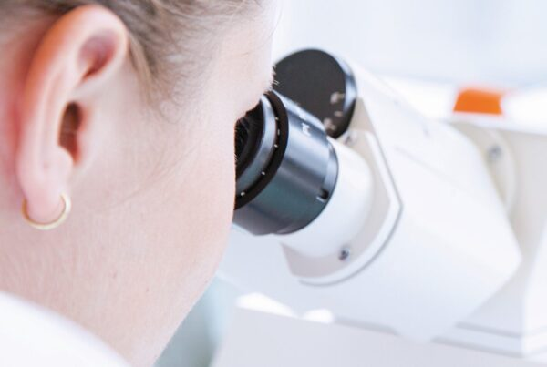 female laboratory worker looking into microscope